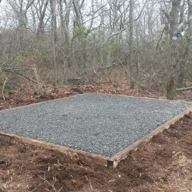 Gravel shed foundation installed in woods