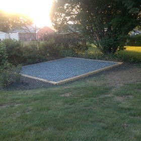 Gravel shed foundation installed in a backyard