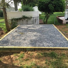 A gravel shed pad installation with a wood perimeter