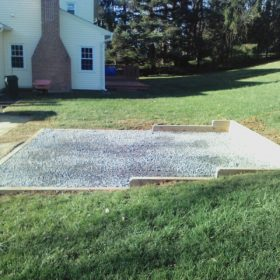 Gravel shed foundation installed in a sloped yard