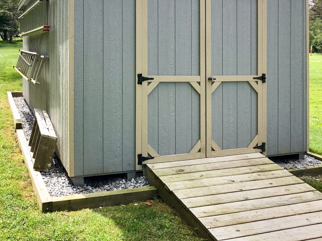 A shed several inches off the ground on a gravel foundation