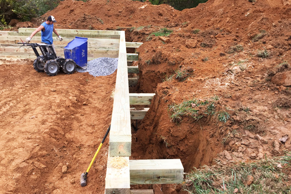 Installation of a large gravel garage foundation with a wooden retaining wall