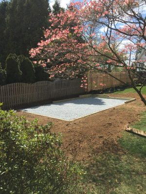 A gravel pad installed for a shed in a backyard